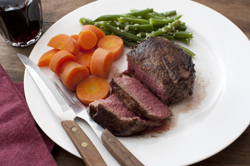 Thick juicy medallion of medium rare fillet steak with fresh carrots and green string beans served with a glass of red wine and utensils