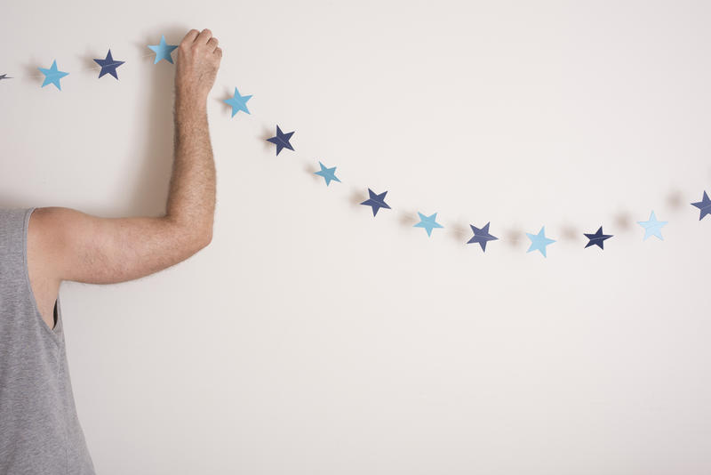 Man decorating his house for a minimalist Christmas hanging a simple string of blue paper stars or bunting on his wall, with copy space