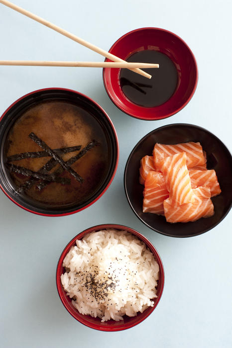 bows of japanese food, soy sauce, salmon and rice with miso soup