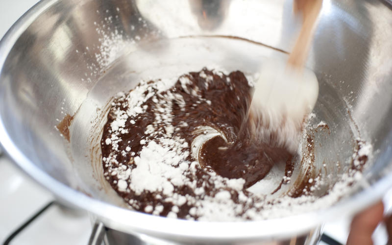 Mixing a bowl of chocolate icing pouring the icing sugar onto melted chocolate and blending with a wooden spoon