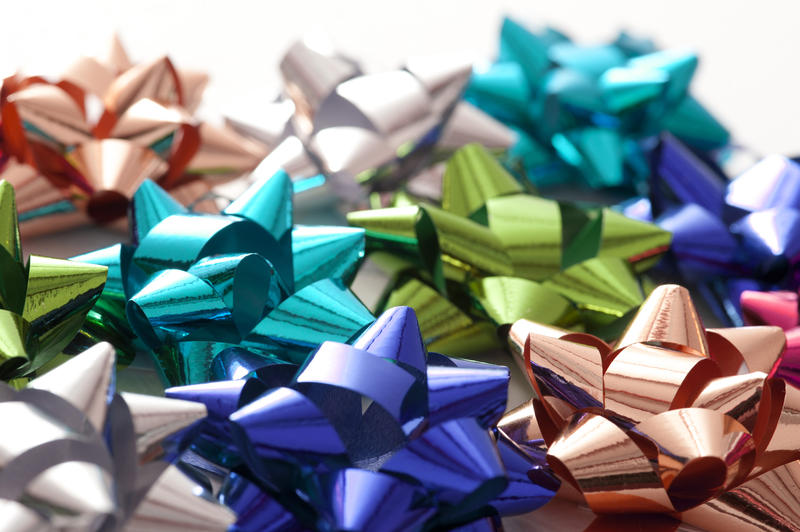 Full Frame Background of Colorful Metallic Gift Bows Scattered on White Background with Copy Space