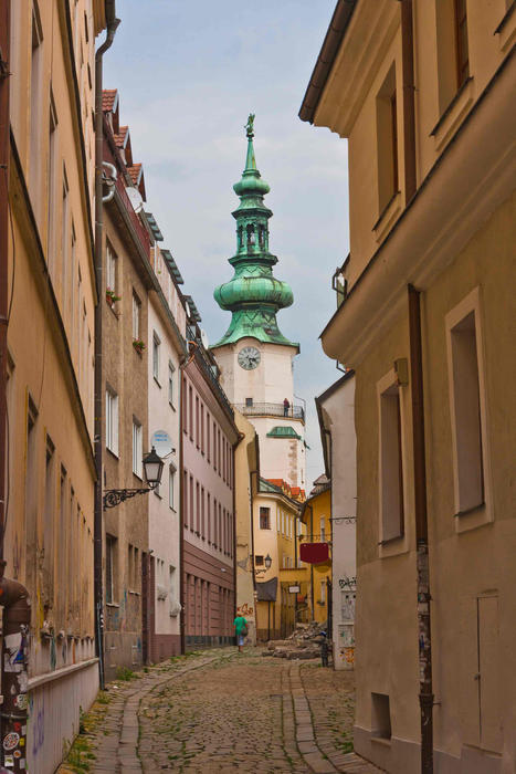 Narrow crooked cobbled bystreet with church tower in Bratislava