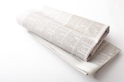 12735   Folded newspapers over neutral color background