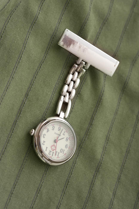 Stainless steel nurses watch with a blank name label pinned to a green striped uniform hianging down on its chain diagonally through the frame