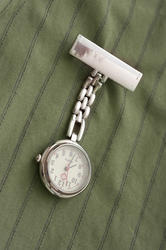12952   Stainless steel nurses watch pinned to a uniform