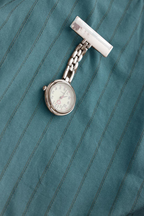 Nurses silver fob watch with a blank name tag pinned on a uniform in a close up view with copy space