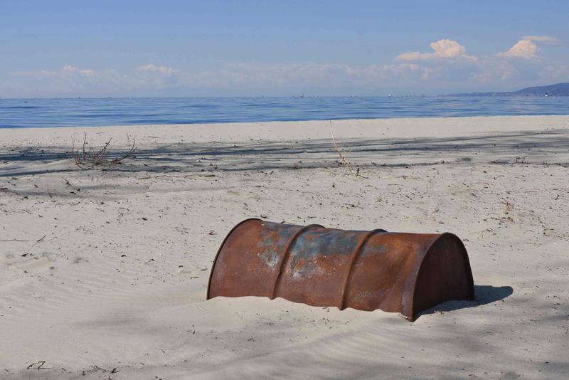 Old Rusty Oil Barrel Buried in Sand, End of Oil Age