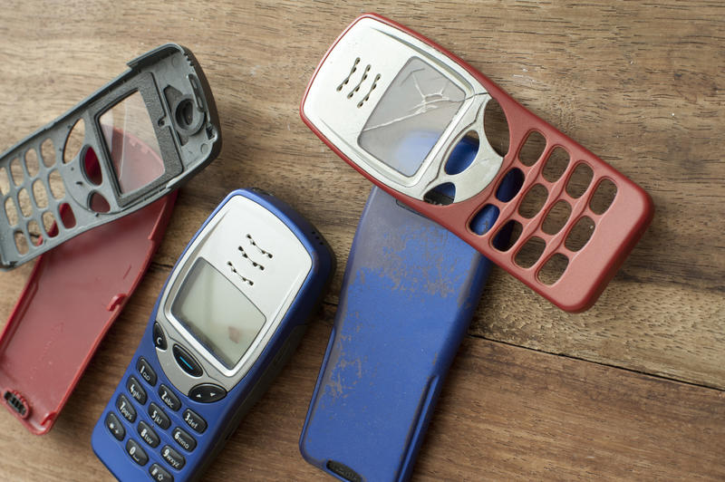 Casings and backs for old style mobile phones with buttons and dials on red , blue and black on a wooden table