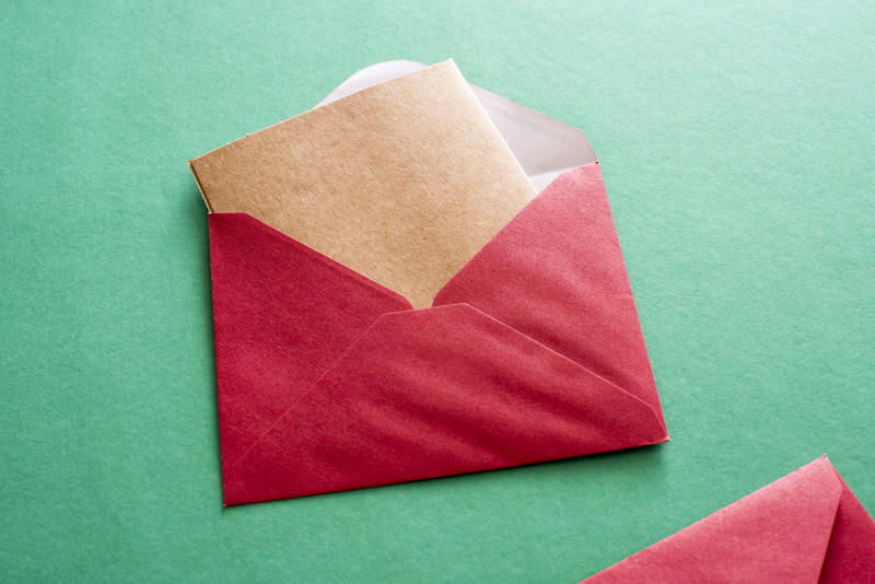 Blank brown card in a red Christmas envelope protruding from the opened flap over a green background with copy space