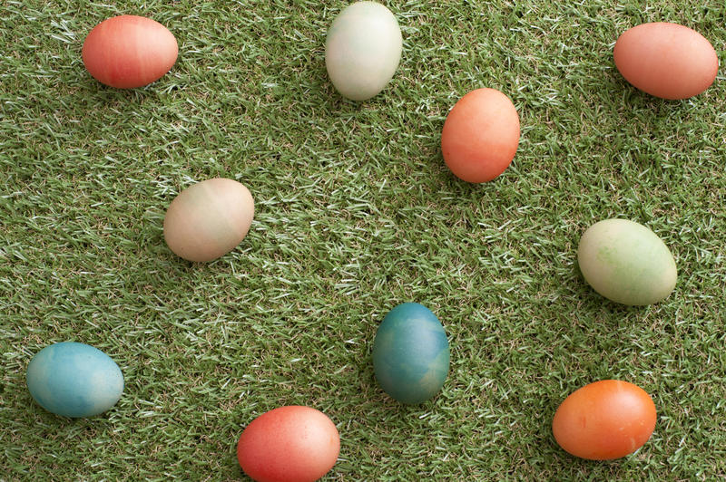 Scattered homemade multicolored dyed Easter eggs on neat short fresh green grass viewed from above in a festive background