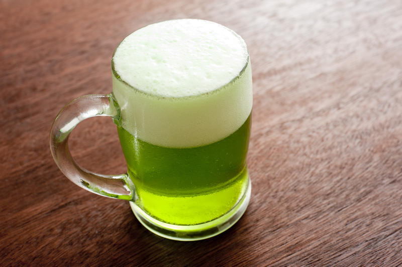 Single glass mug full of beer with green coloring and white foam on top above wooden table