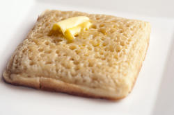 12272   Buttered wheat crumpet on plate
