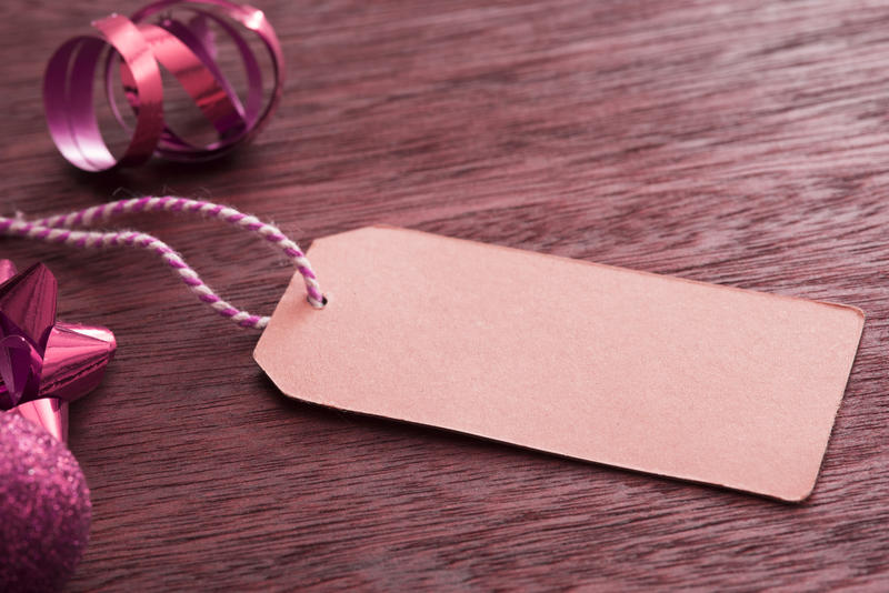 Blank gift tag with Christmas packaging items such as a red twirled ribbon and spiky bow forming a side border on textured wood