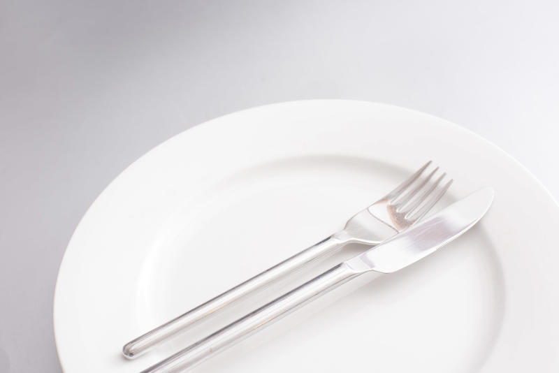 Clean generic white dinner plate with silver knife and fork neatly arranged in the centre in a close up cropped view