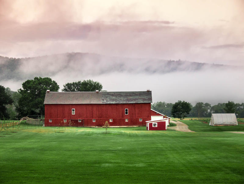 <p>Red Barn, fog, clouds and green grass rural Vermont.</p>