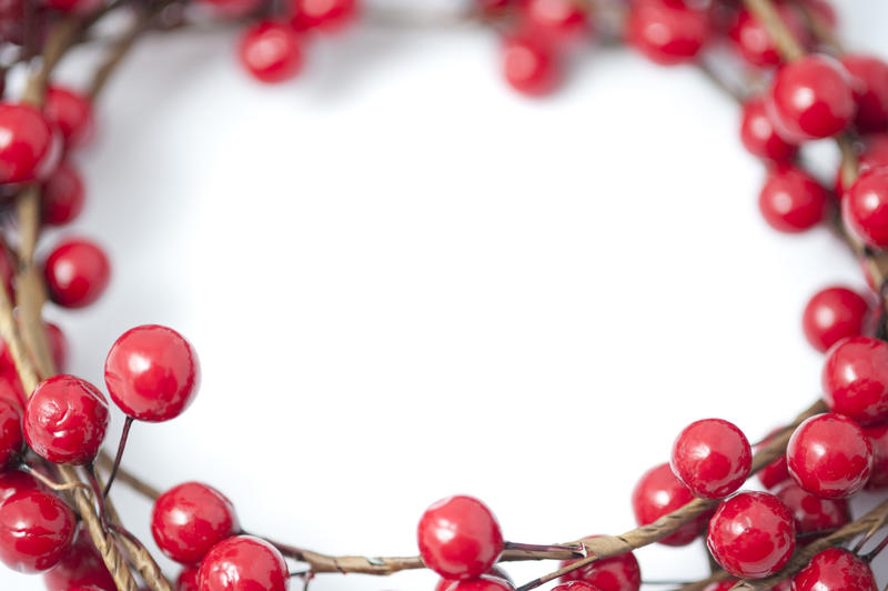 Border, wreath or frame of artificial festive red Christmas berries around central white copy space for your holiday message