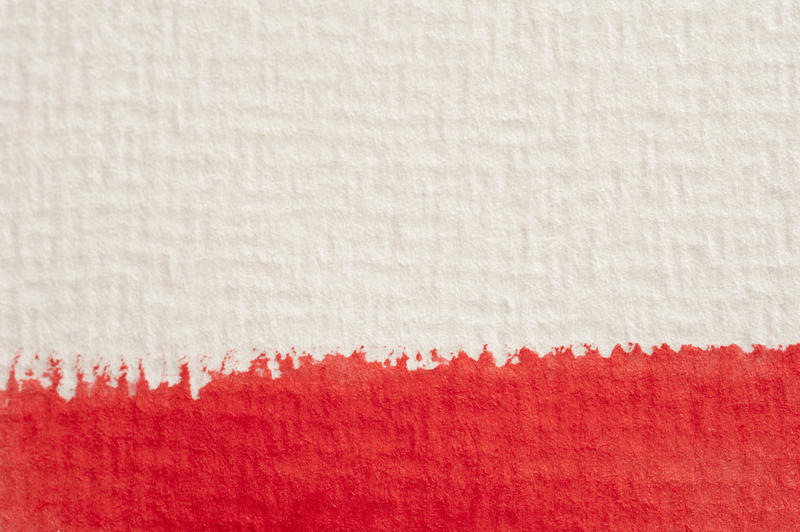 Extreme macro close up view on thick red watercolor paintstroke on textured canvas paper