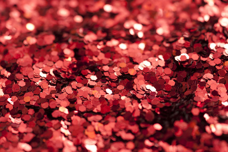 Background texture of sparkling red glitter in a close up macro view with shallow DOF for a festive or craft concept