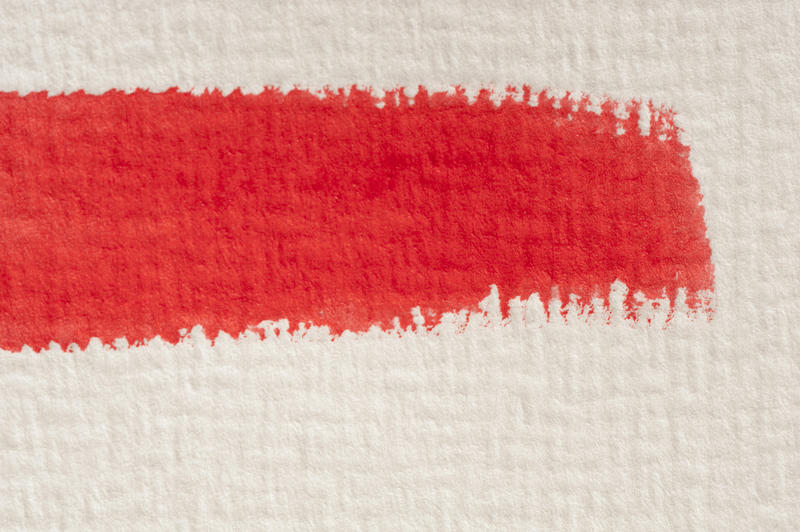Close up detail of a single red watercolor paint brushstroke on textured paper or canvas with copy space below
