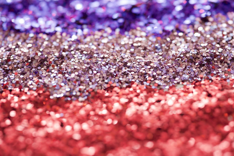 Extreme Close Up of Sparkling Glitter Background Arranged in Colors of Red, Pink and Purple - Celebratory Sequin Background Arranged Full Frame in Stripes in Selective Focus