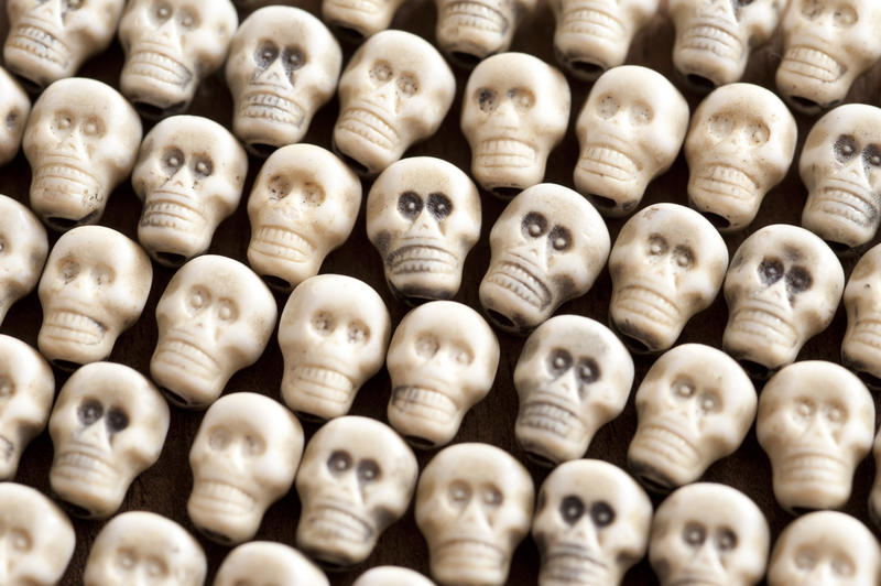 Neatly arranged white plastic skull background for Halloween, horror, piracy, death or genocide themed concepts in a close up full frame view