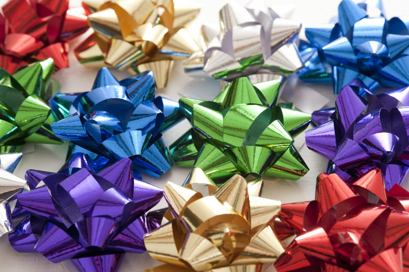 Multiple colorful decorative bows made from shiny ribbon for decorating festive gifts and packaging, full frame view