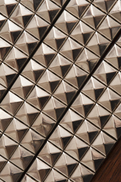 Background texture of pyramidal silver studs in a repeat pattern with oblique lighting enhancing the shape