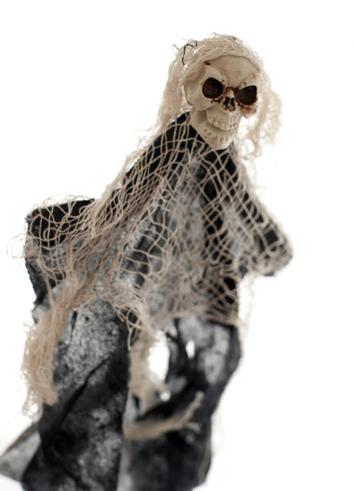 Cute skeleton witch puppet in black cloth, netting and plastic skull over white background