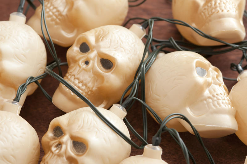 Bundle of plastic toy skull party lights for Halloween in a close up view in a tangle of wires with focus to the central face