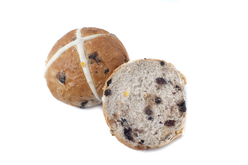 Close up view of sliced hot cross bun with raisins, and one whole bun marked with white cross, isolated on white background