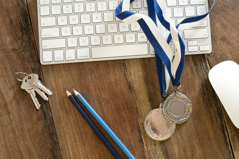 Online sports award concept with two sporting medals lying across a computer keyboard on a wooden desk, high angle view