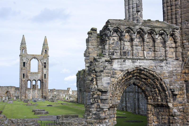 Green grass surrounded by arches and tower at Saint Andrews Cathedral in Scotland, Europe