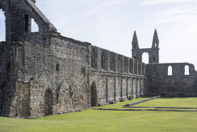 World famous stone wall remains of the historic Saint Andrews cathedral surrounded by green grass in Scotland