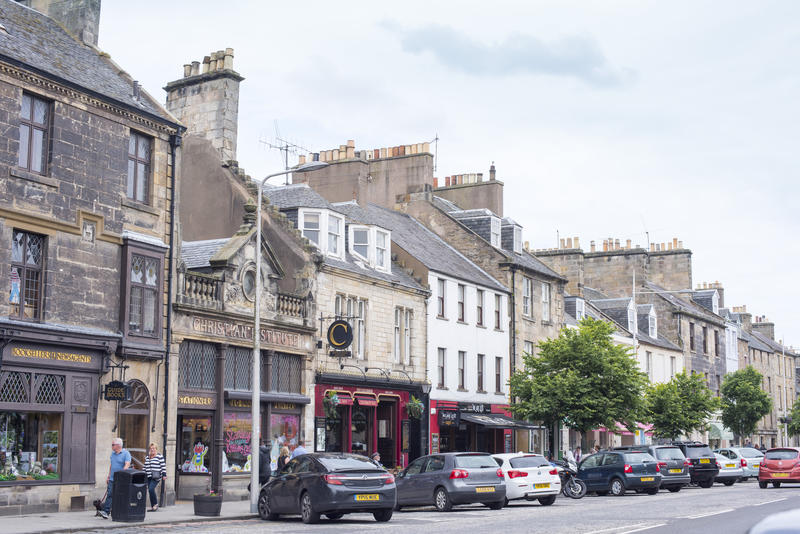 Various parked cars and tourists along busy small town street in Saint Andrews Scotland