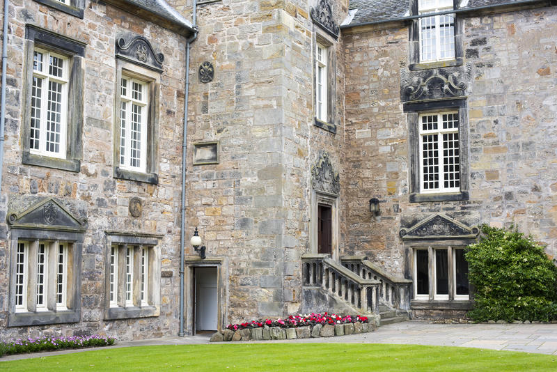View across a manicured lawn to entrance stairs to one of the historic stone buildings at St Andrews University, Scotland