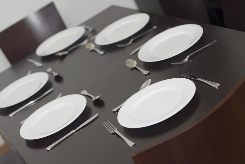 Dinner table laid for a family meal with cutlery and generic white dinnerware viewed at a tilted angle