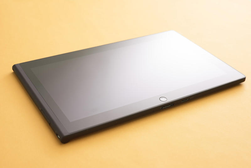 Tablet mobile device with blank black screen close-up on yellow surface with studio lighting