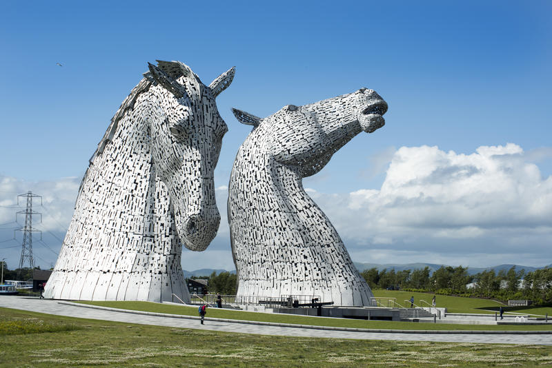 Small people walking along paths past the Kelpies statues in Falkirk Scotland