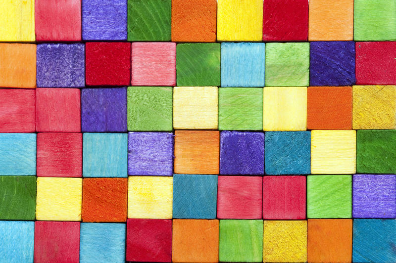 Colorful background texture of wooden toy building blocks in the colors of the rainbow neatly arranged in rows in a full frame view