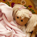 11979   Doll Nestled Under Blankets in Wooden Cradle