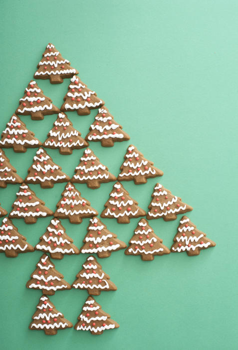 Gingerbread Christmas tree still life with traditional tree shaped Xmas cookies arranged on a green background with copy space