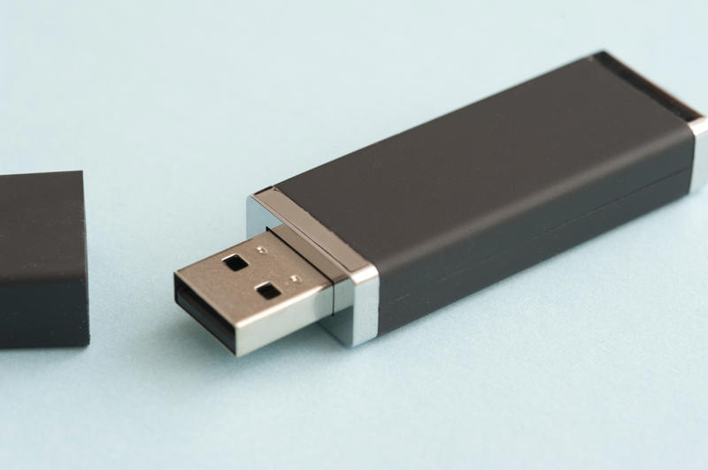 Single black USB drive or memory stick for a computer lying on a light blue background with the cap off