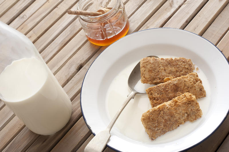 Three wheat biscuits of breakfast cereal in milk with spoon besides glass bottle and jar of honey