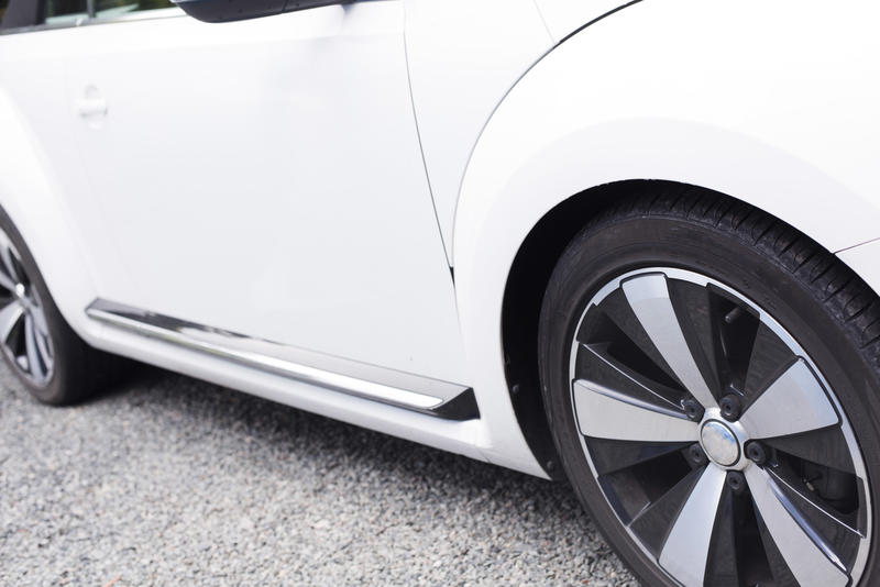 Close up view of the side of a white car showing the coachwork and tyre with spokes on the rim parked on asphalt