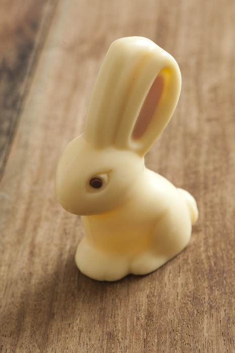 Close up view of white chocolate easter bunny sitting on wooden table surface background