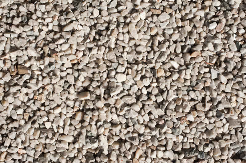 Close up overhead view of light colored gravel illuminated by a bright afternoon sun