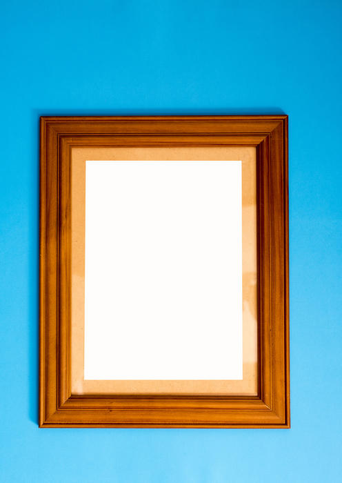 Blank empty rectangular wooden picture frame on blue for your artwork or photo