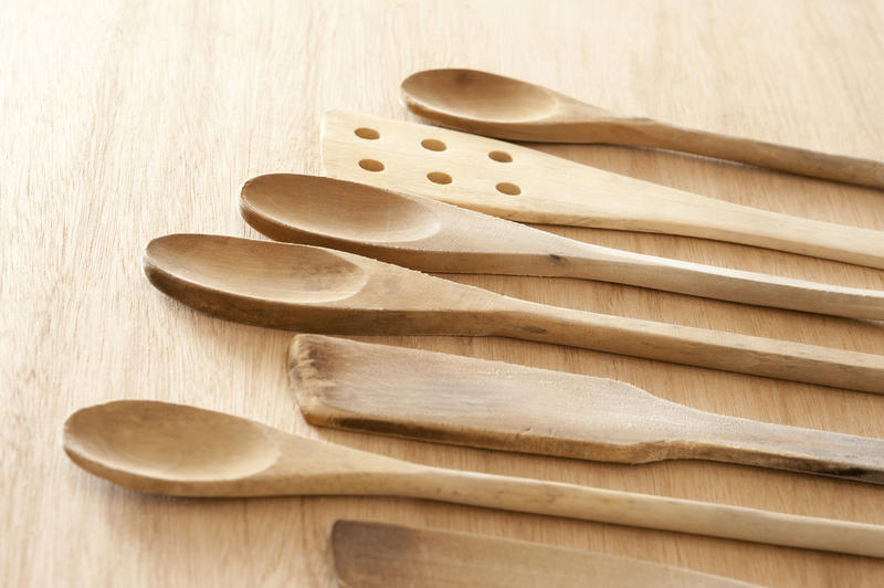 Set of wooden kitchen spoons and spatulas laid out in a neat row on a wooden cutting board or table