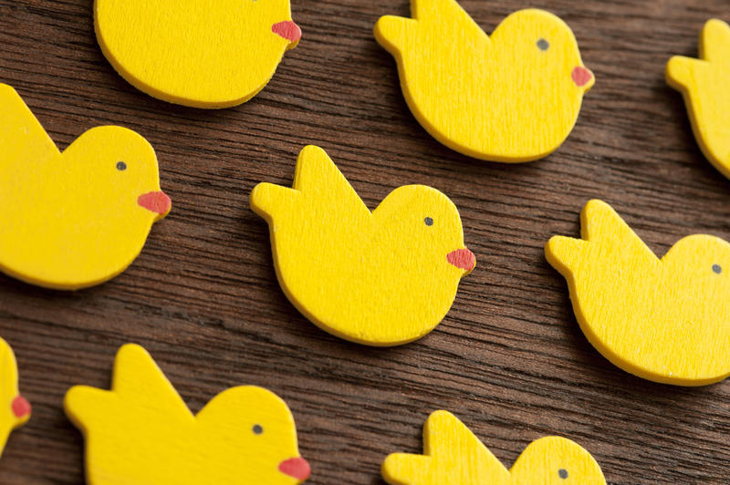 Rows of yellow wooden shapes of small Easter chicks decorations or toys over lacquered table surface background