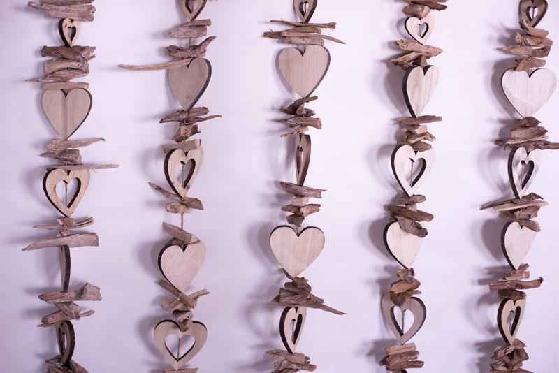 Wooden colourless heart shapes strung on strings, hanging close to pink background as vertical lines. Background concept
